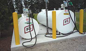 Picture of two farm fuel storage tanks sitting on a concrete pad.  The storage site has 3 bollards across the front of the tanks to prevent vehicles from hitting the tanks. Tanks have electric fuel pumps that are properly wired with totally enclosed fixtures.
