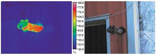 The photo on the left is a thermographic (uses colour to indicate hot spots) image of an exhaust pipe venting to the outside through the barn wall.  There is no heat shield between the pipe and the wall and the exhaust pipe is showing temperatures of 75°C.  The photo on the right is the actual picture of the same exhaust pipe venting through barn wall and without a heat shield to prevent heat damage or fire in the wall.