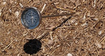 Picture of a circular thermometer placed in a pile of compost.