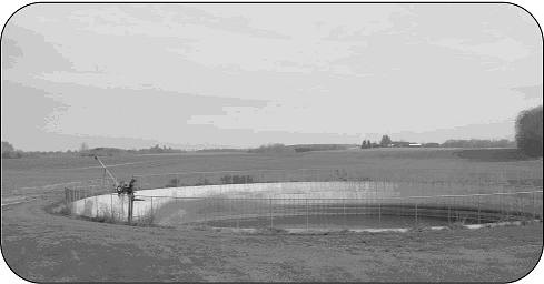 Image shows an overall view of a  large circular manure storage tank situated in a pasture.