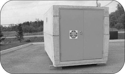 This is a photo of a prefabricated, square-shaped pesticide storage unit that is sitting slightly raised off the ground.
