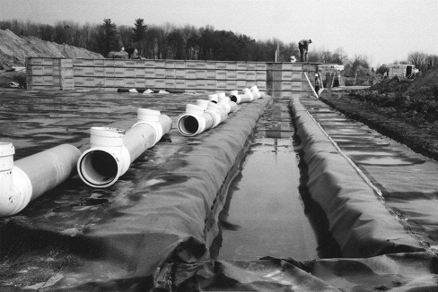 Photo of PVC pipe sections lying to the side of a trench that will eventually be connected to form a secure liquid manure transfer system from the in-barn tank to the external manure storage.