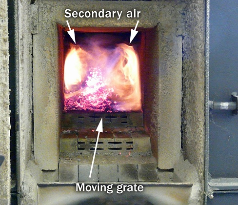 The picture shows the combustion chamber of the boiler installed at the Ithaca Campus of Cornell University. The flames are a bright orange near the secondary air ports, demonstrating a higher combustion temperature.