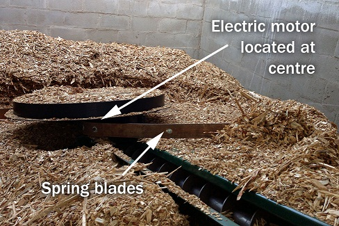 The picture shows a rotative extractor handling waste wood in a vertical biomass storage.