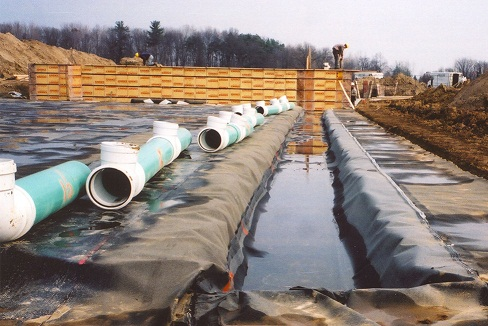 This picture shows PVC pipe sections lying on the ground waiting to be  connected together to form a secure liquid manure transfer system from the in-barn tank to the external manure storage.