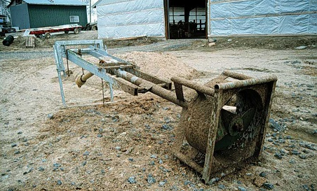 Picture of a propeller agitator pump sitting on the ground in front of a farm building.