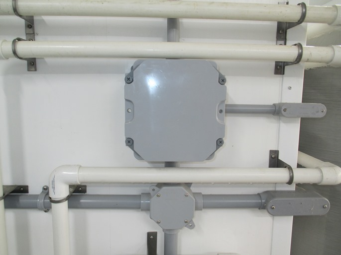 This is a photograph of a NEMA4X rated electrical enclosure mounted the wall of a barn.  The enclosure is made out of grey plastic.  There are no holes or vents in the enclosure that would allow moisture or corrosive gases to enter.  The electrical wiring entering the enclosure is all housed in plastic conduit.