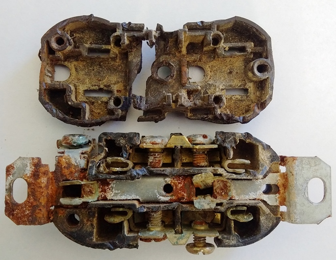 This is a photograph of a standard electrical receptacle which had been in use in a dairy barn.  The receptacle has been split open to display severe corrosion of its internal copper components.