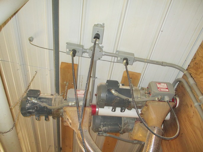 This is a photograph of three electrical motors mounted off the ceiling in a dairy barn.  The three motors are all totally enclosed frames with integral cooling fans.  Electrical power is supplied to motors through a common 220V plug inserted into a receptacle mounted on the ceiling.  The receptacle is installed in a sealed plastic enclosure.  The wiring supplying power to the receptacle is all installed in sealed plastic conduit.