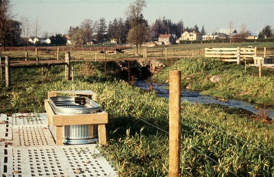 Alternate watering station for livestock with reinforced base beside fenced watercourse. Mid-level crossing in foreground allows livestock to travel to pasture on both sides of watercourse.