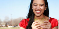 photo of a girl eating a sandwich